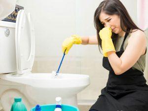 mulher mexendo na privada tampando o nariz por conta do mau cheiro