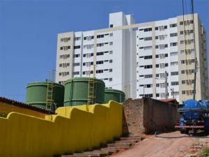 Foto de um sistema de esgoto e ao fundo um condomínio de prédios