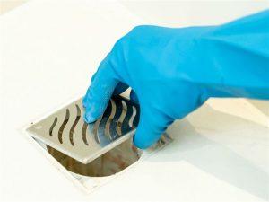 Mão de uma pessoa com uma luva de limpeza retirando a tampa de um ralo