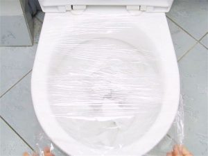 Vaso sanitário visto de cima com filme plástico como meio para desentupir