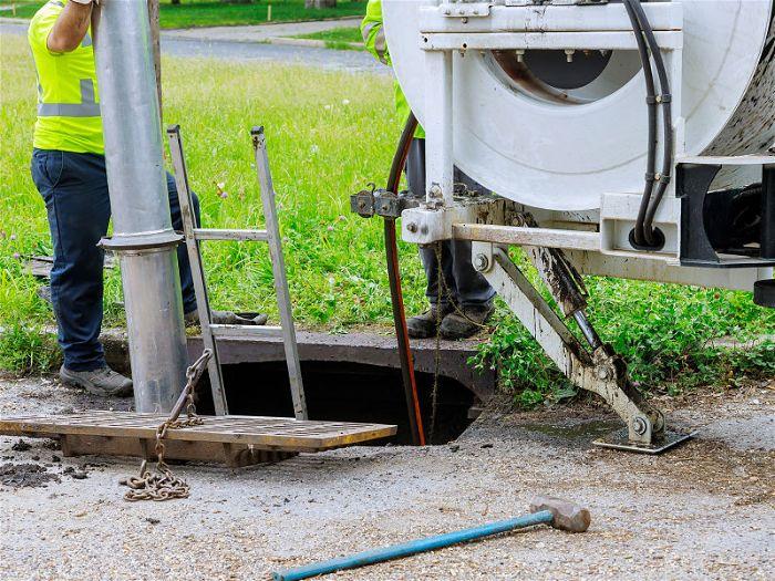 Caminhão ao lado de uma fossa realizando esgotamente de uma fossa septica