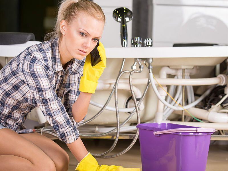 Mulher abaixada com luva de limpeza, ao lado de balde