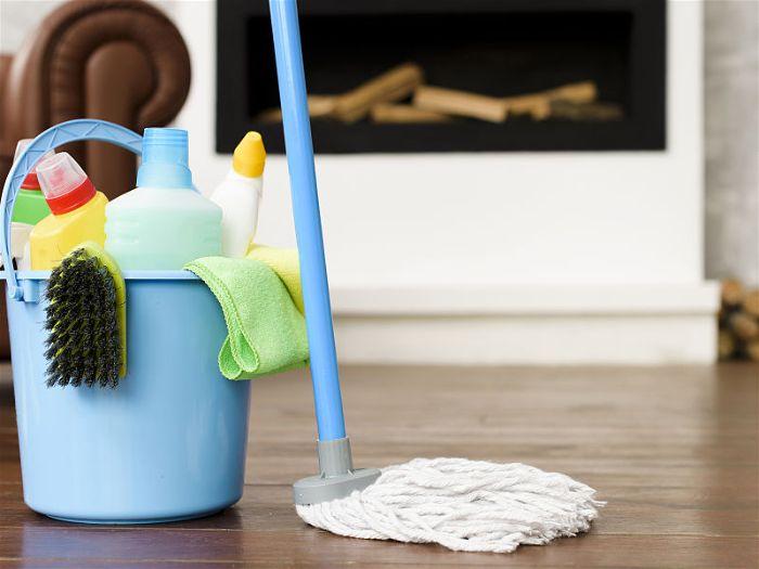 Balde de limpeza com produtos dentro e um esfregão ao lado