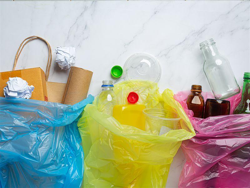 Sacos de lixo de diversas cores, cada um com um tipo de lixo descartável