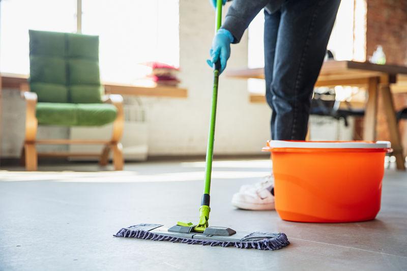 Pessoa passando pano no chão de um ambiente de casa