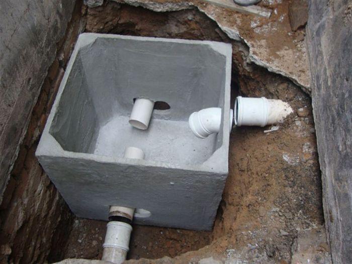 Foto de uma caixa de gordura aberta em construção no chão