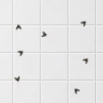 Azulejo branco de banheiro com diversas moscas