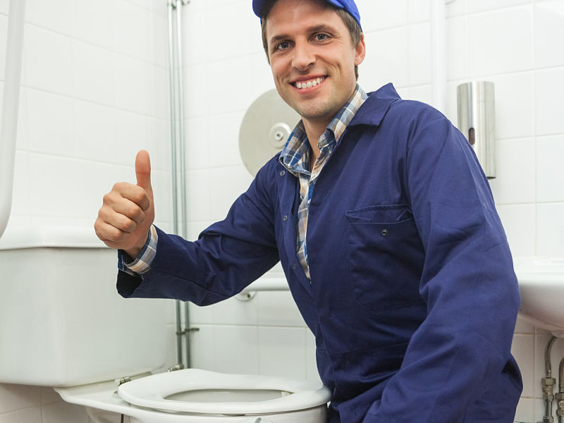Homem com roupas adequadas para o trabalho de encanador em frente vaso sanitário fazendo sinal de positivo