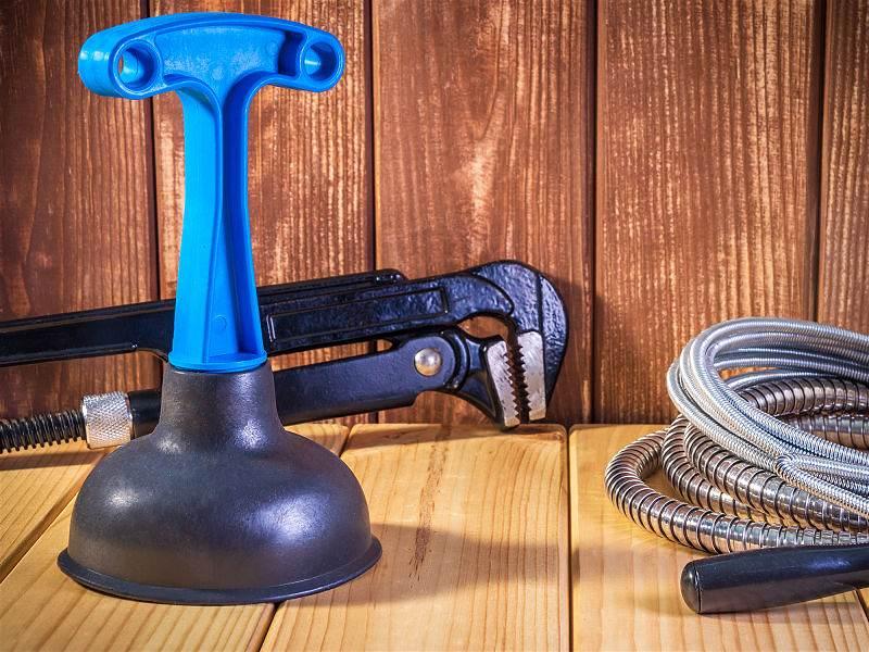 Equipamentos para manutenção de vaso sanitário sobre local de madeira
