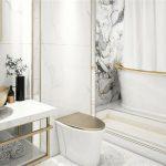 Imagem de banheiro com peças e azulejos com tom claro e detalhes dourados