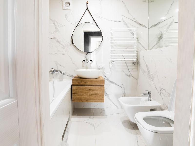Imagem de banheiro com peças e azulejos brancos, com espelho em formato de gota, bem como bancada suspensa de madeira
