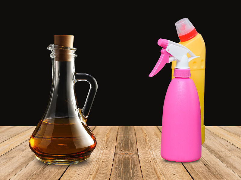 Imagem fundo preto e frasco de produto de limpeza e de vinagre sobre mesa de madeira