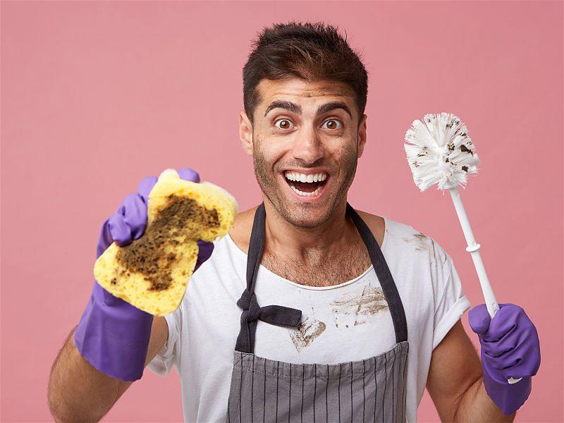 Banner com fundo rosa e homem ao centro com cara de felicidade segurando em uma mão espoja suja e na outra uma escovinha para limpar vaso sanitário
