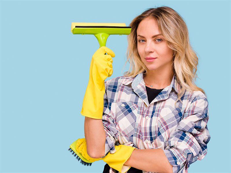 Mulher utilizando luva de limpeza com um braço apoiado no outro segurando rodinho próximo a cabeça