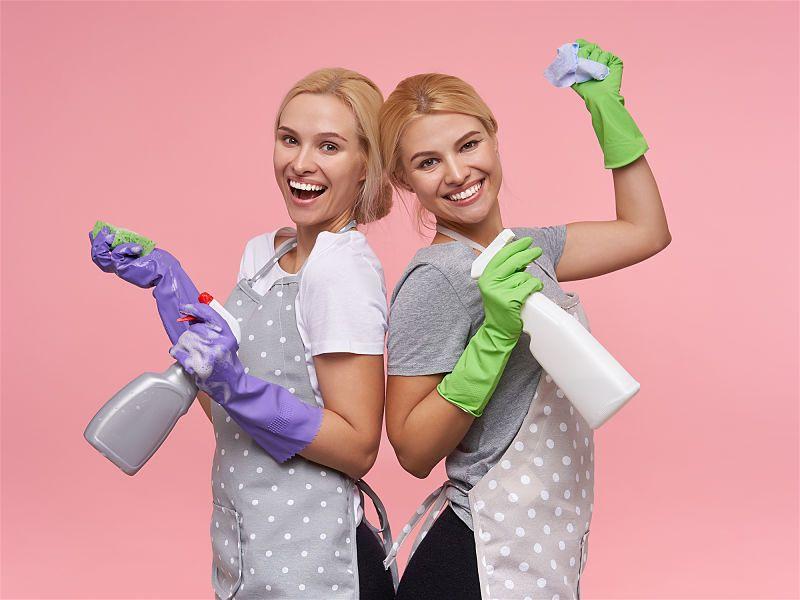 Banner com fundo rosa e duas mulheres sorridentes uma de costa para outra utilizando luvas de limpeza e segurando frasco de produto de limpeza