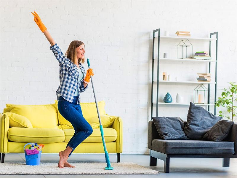 Mulher com luva para fazer limpezas, em sala de estar, com um braço erguida e outro segurando um rodo e utilizando como se fosse um microfone para cantar