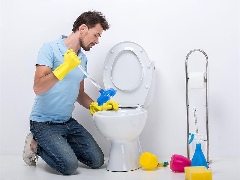 Homem ajoelhado em frente vaso sanitário com luvas e desentupidor em mãos