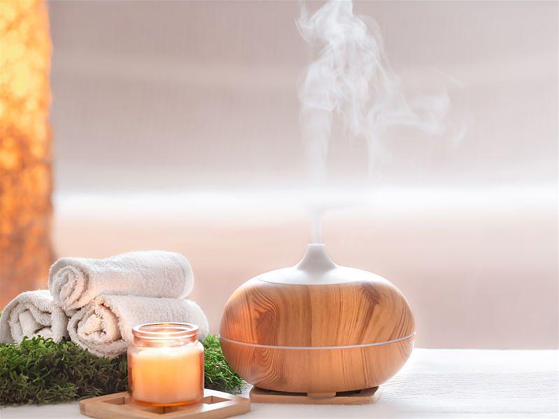 Imagem com recipiente aromatizando ambiente com vapor ao lado de toalhas enroladas e vela dentro de recipiente de vidro