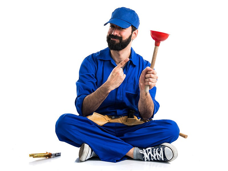 Homem vestido com roupa de encanador, sentado no chão, segurando desentupidor de pia