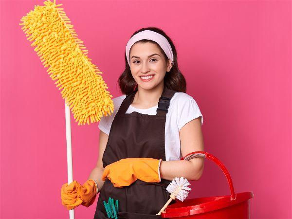 Mulher com segurando produtos de limpeza